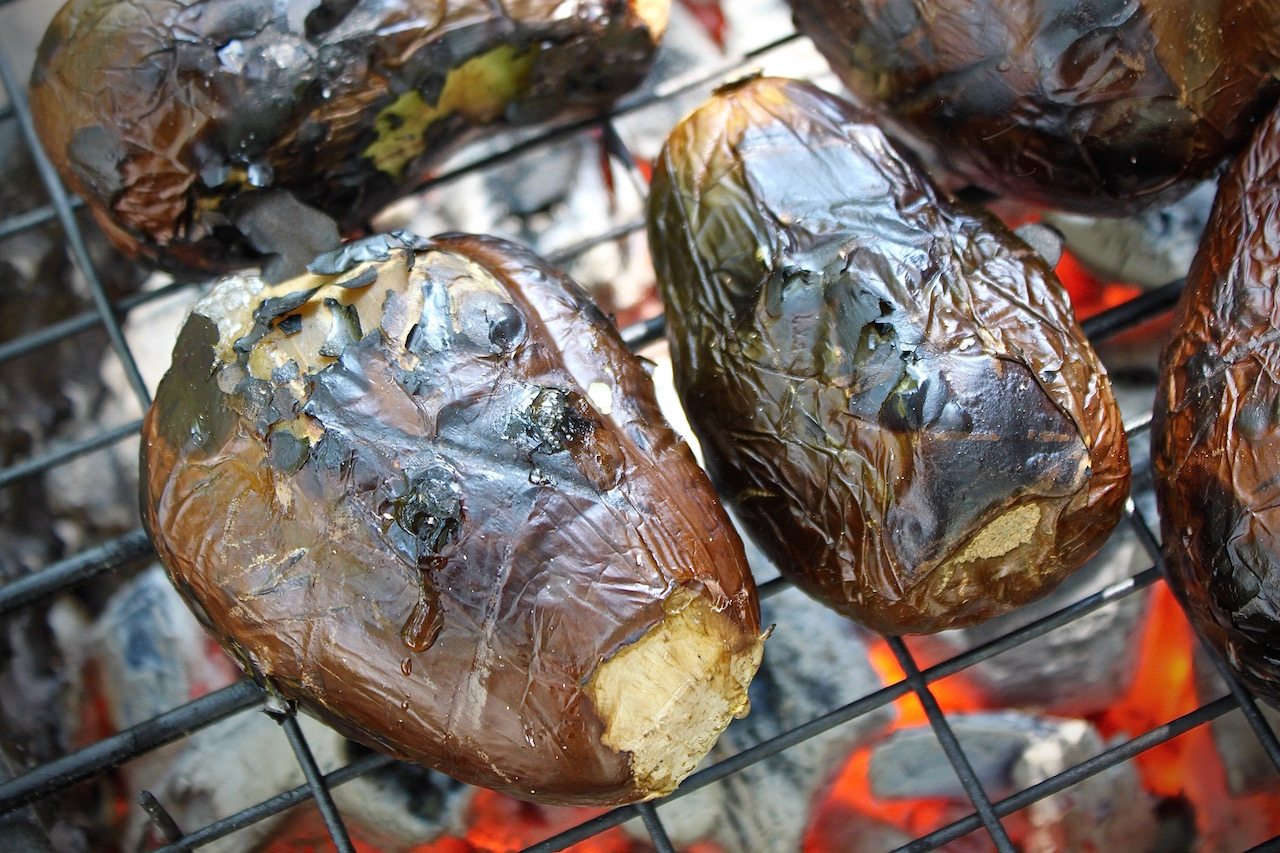 Roasting the aubergines over the coals on the mbaula.