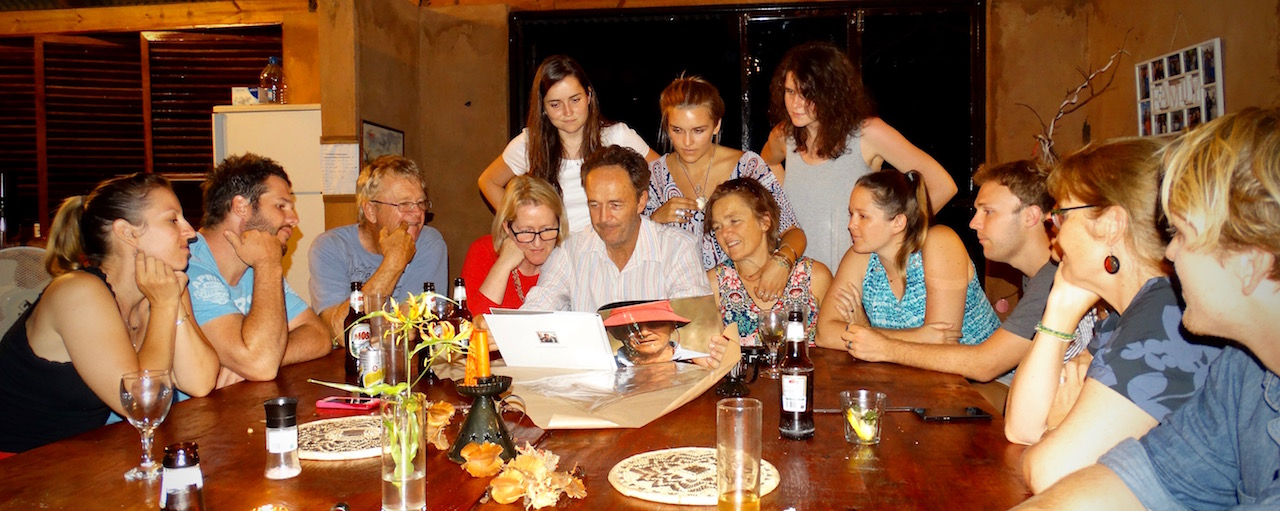 Chris, surrounded by his children and siblings, looking at a book of family recipes, made for him by his sister, Dee.